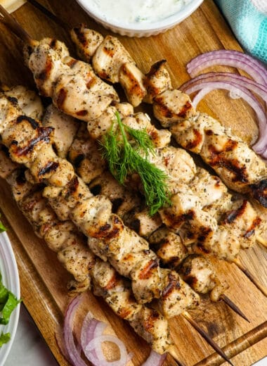 Top view of chicken souvlaki on a wood cutting board.