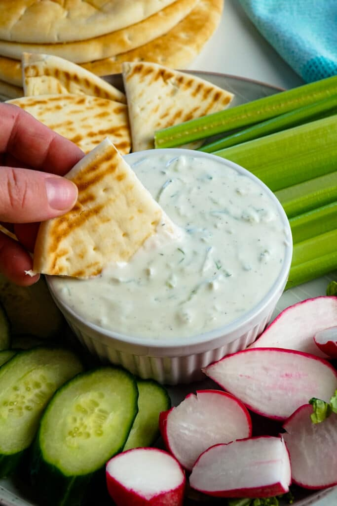 Tzatziki Sauce with fresh pita bread being dipped into it.