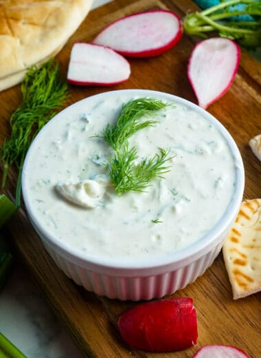 Close up of Tzatziki sauce in a white bowl and garnished with fresh dill.