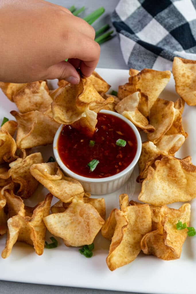 Crab Rangoon being dipped into sweet chili sauce.