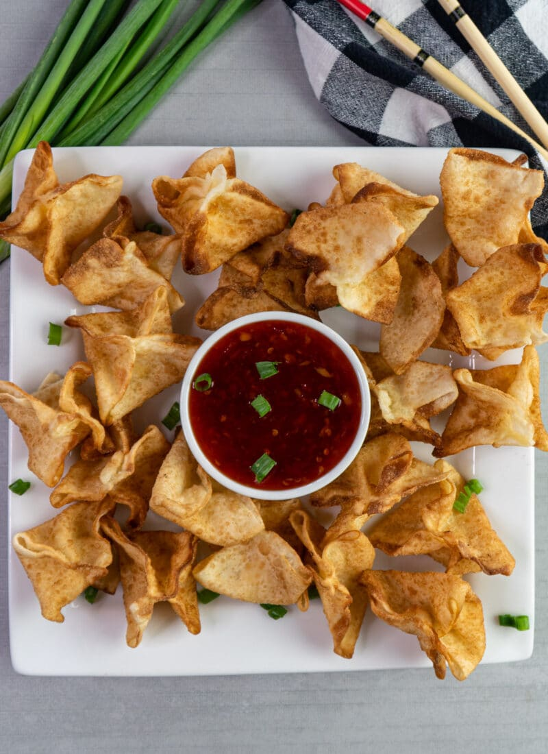 Cream cheese crab rangoons on a plate with sweet chili sauce.