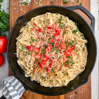 the most amazing Cajun chicken alfredo recipe served with diced tomatoes and chopped parsley