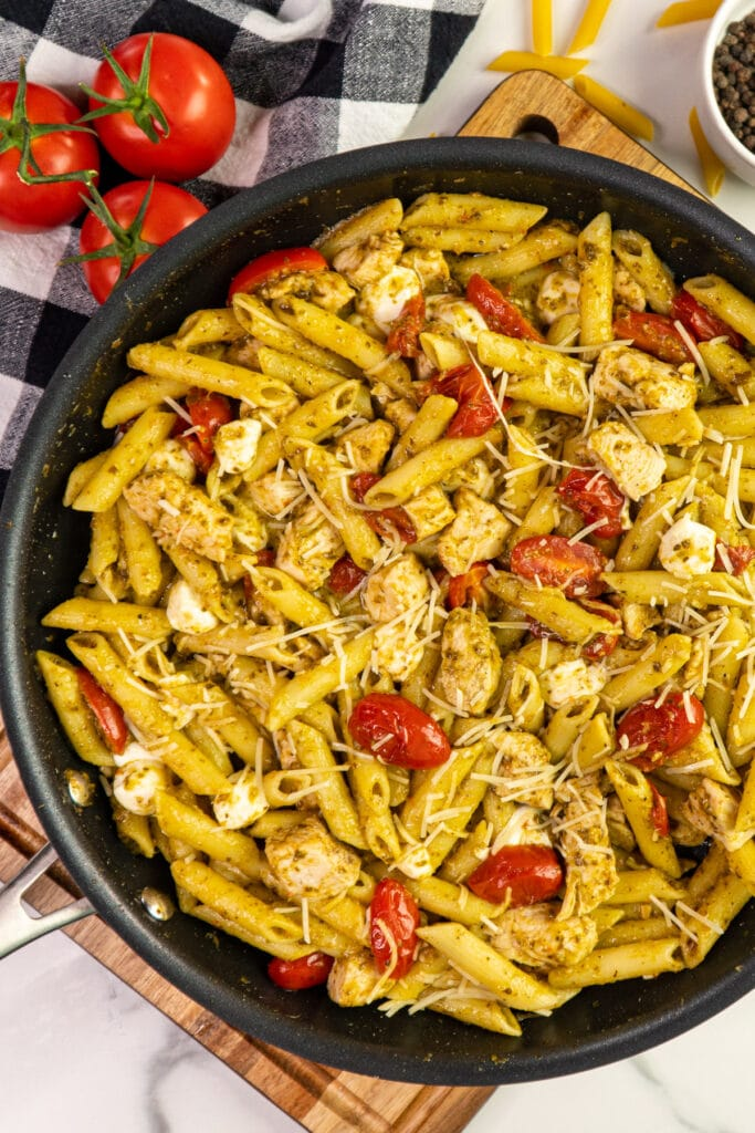 Chicken pesto pasta in a skillet and garnished with shredded parmesan cheese.