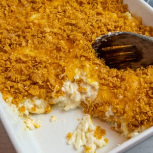 Funeral potatoes in a white baking dish with a wooden spoon scooping out the potatoes.