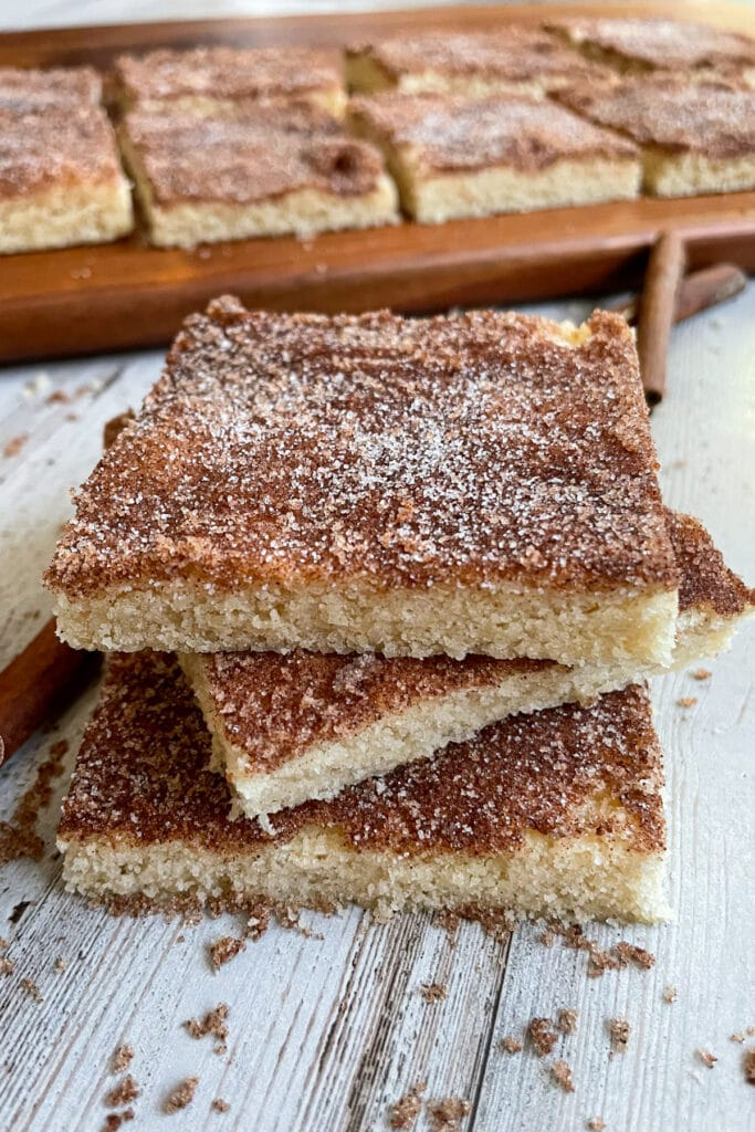 The best soft and chewy snickerdoodle cookie bars stacked on top of each other
