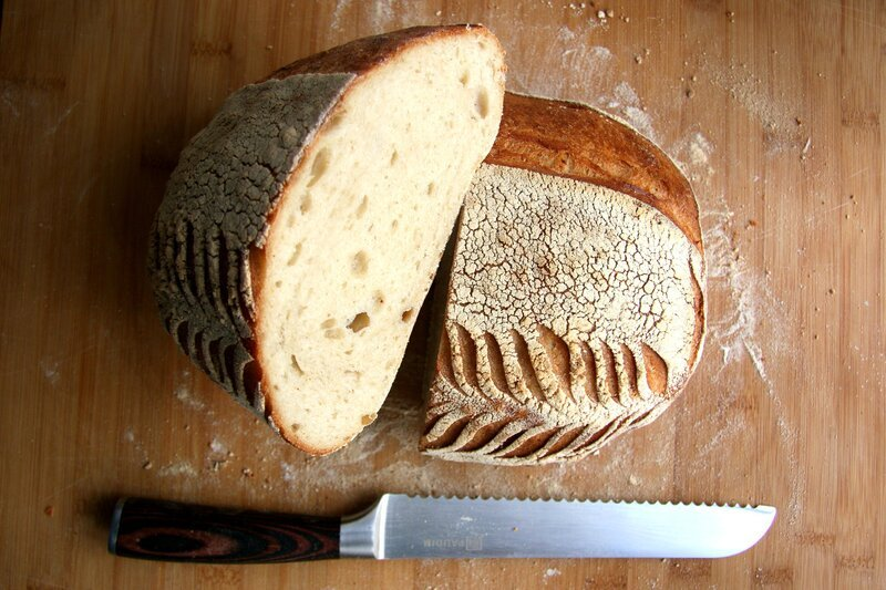 bread on wooden chopping board with knife