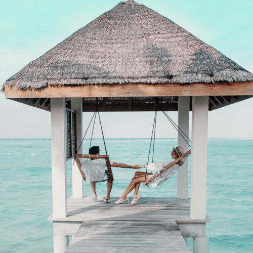 Woman and Man by Ocean in Cabana