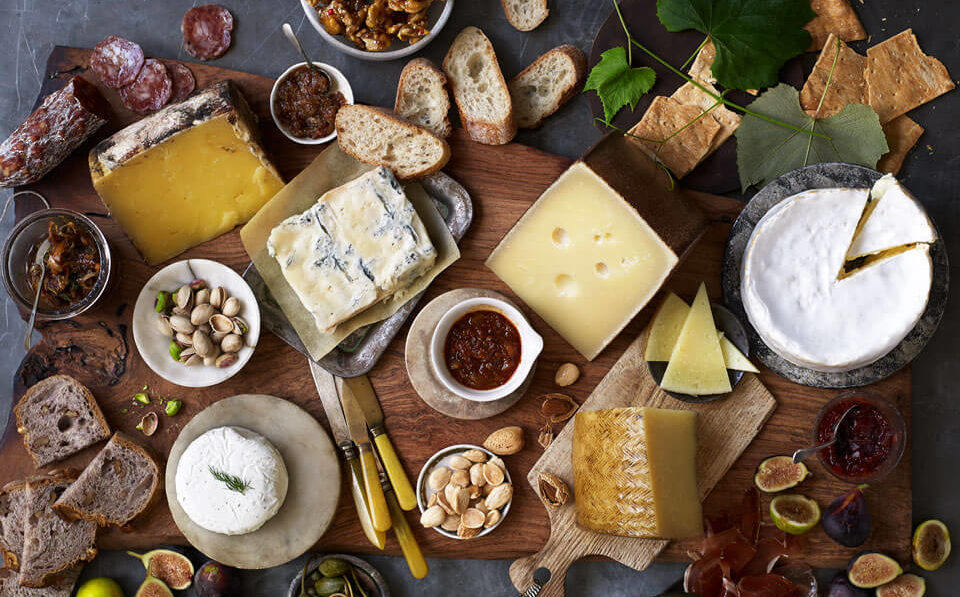 National Wine and Cheese Day Cheeses, nuts and bread on wood board