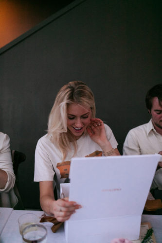 Blonde Women Smiling, Opening OuiPlease Box at Table