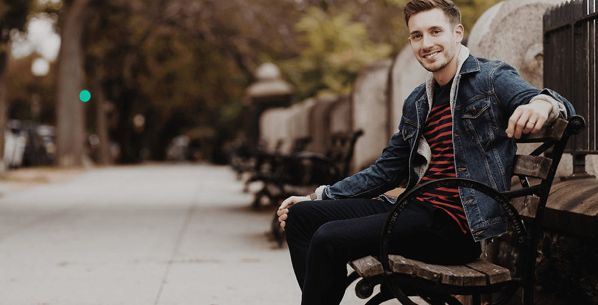 Men seating on a bench with stripe shirt and jeans jacket smiling