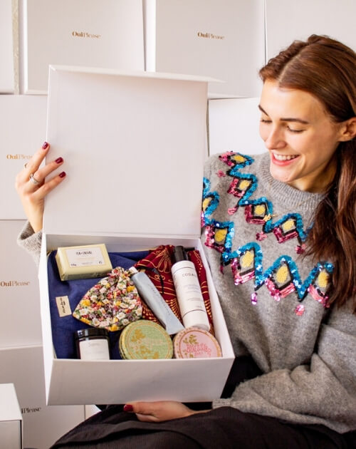 woman holding open ouiplease box
