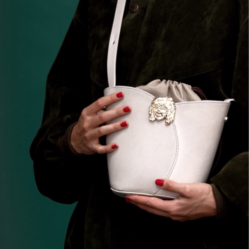 woman holding a white handbag with clasp