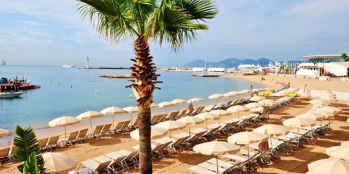 Cannes beach with large white umbrellas and chairs