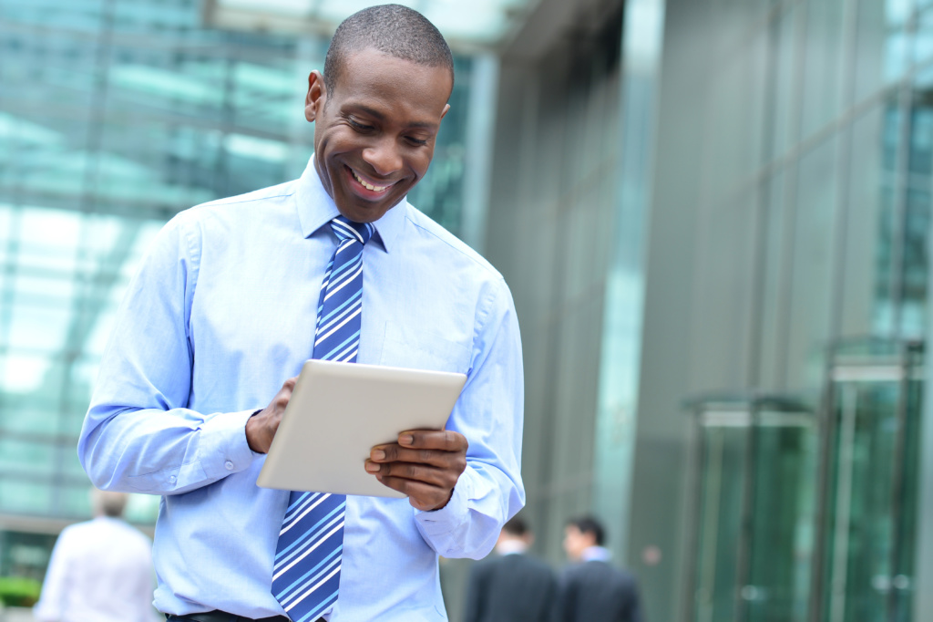 Smiling businessman using his new digital tablet