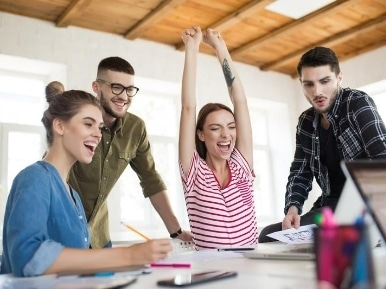 Group of cheerful business men and women happily working together 1