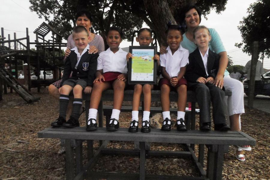 Above: Grade 1 pupils and teachers sit on the new picnic bench made from recycled plastic that they received as their prize in Plastics SA's Clean-Up and Recycle Competition, whilst proudly showing off their certificate.
