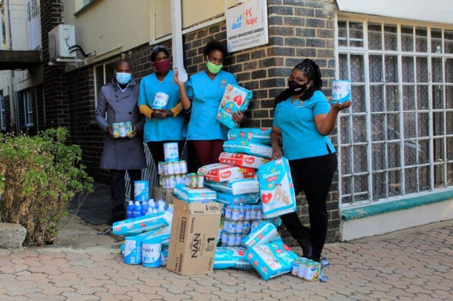 Claude Boni, far left, and Door of Hope staff with the donation from OSTI