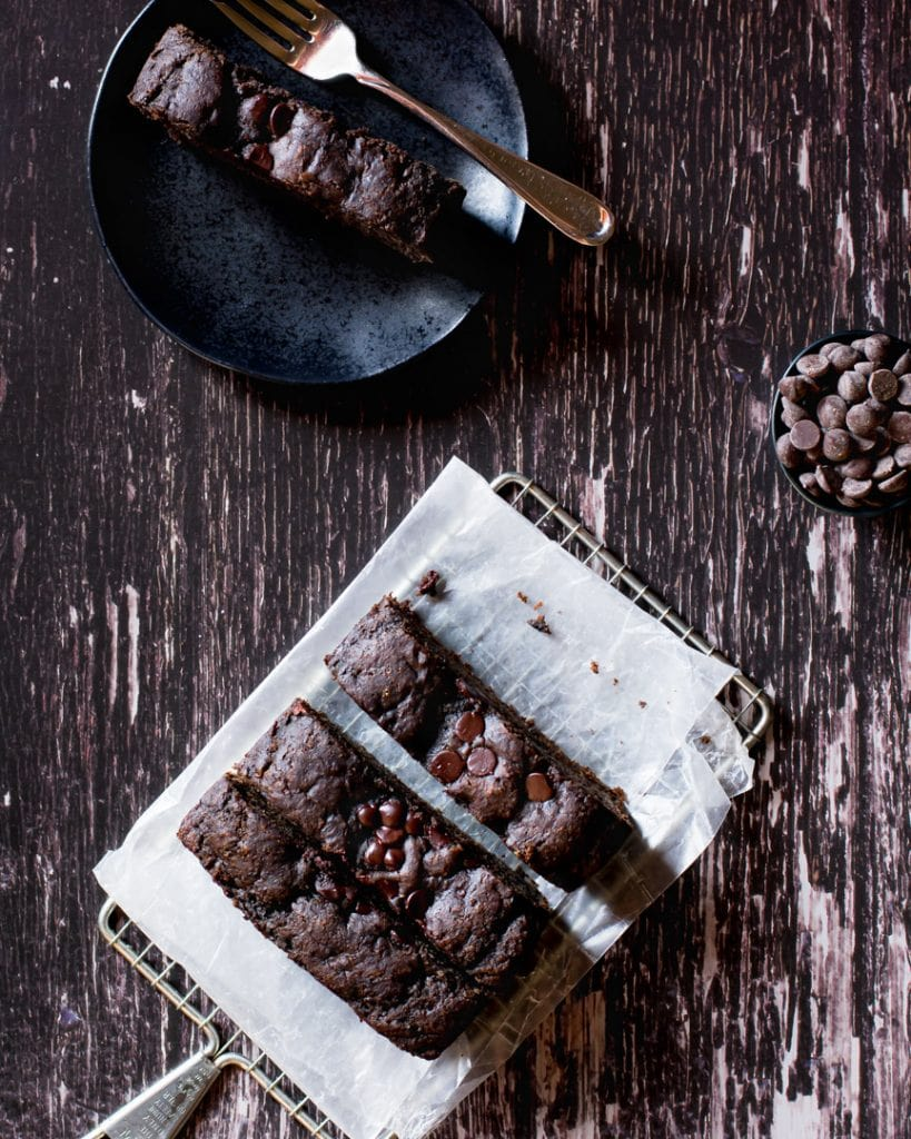 banana tahini bread with slice on plate and bowl of chocolate chips