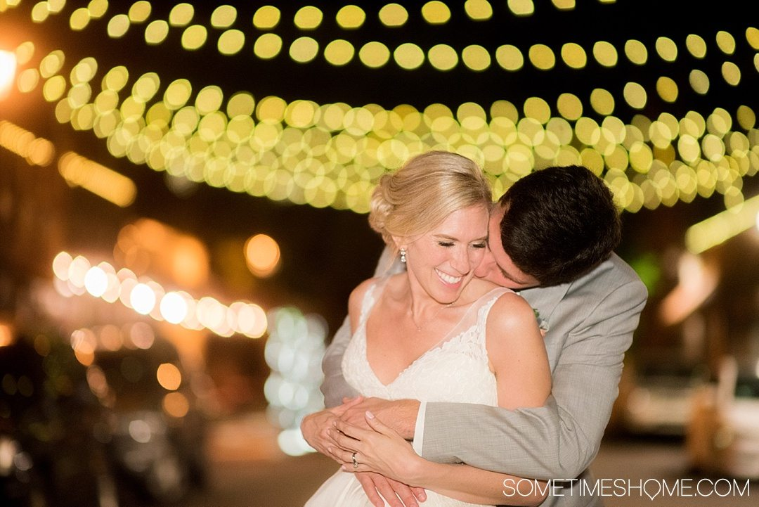 10 Best Downtown Raleigh Photography Spots on Sometimes Home travel blog. Photo of City Market cobblestone street with strung overhead lights with a bride and groom.