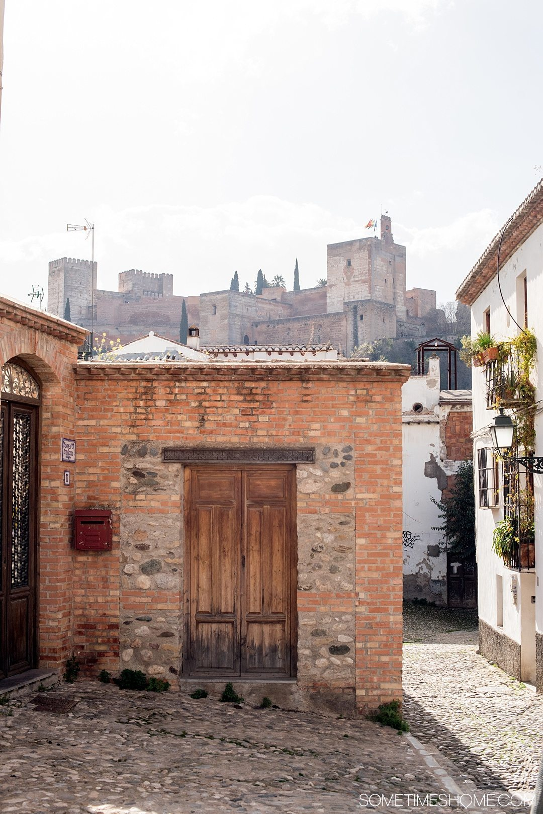 One Perfect Day in Granada Spain. Photos and itinerary on Sometimes Home travel blog. Picture of the view from Cafe Gatos, where you can see the Alhambra.