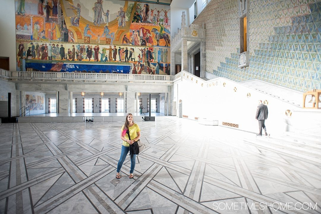 10 Not-to-Miss Sites in Oslo Norway by Sometimes Home travel blog. Photo of the colorful interior of Oslo Radhus, City Hall.