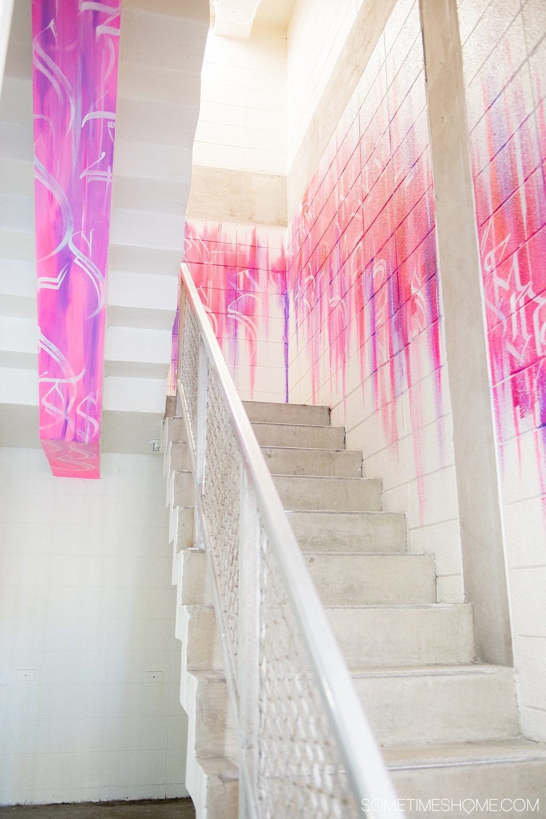 Unscripted Hotel Review Durham in North Carolina. Photos and information on Sometimes Home travel blog. Picture of the pink and purple graffiti painted staircase.