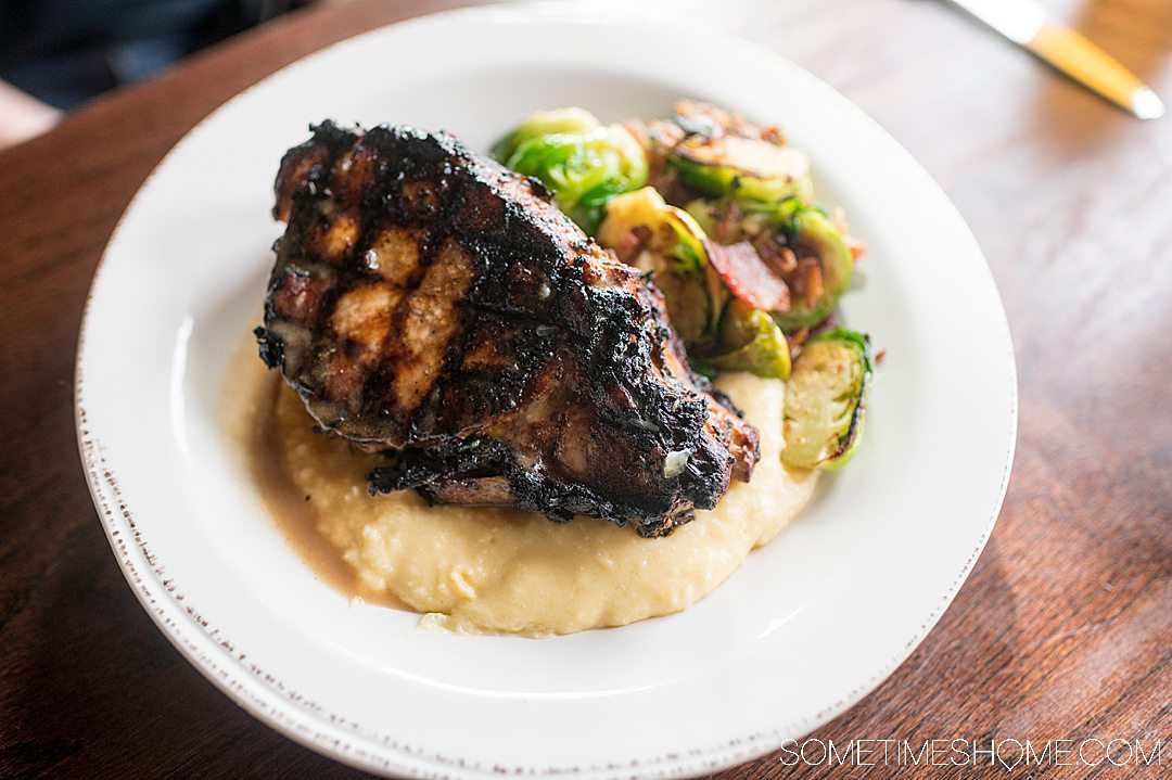 Grilled pork chop, grits and Brussels sprouts.