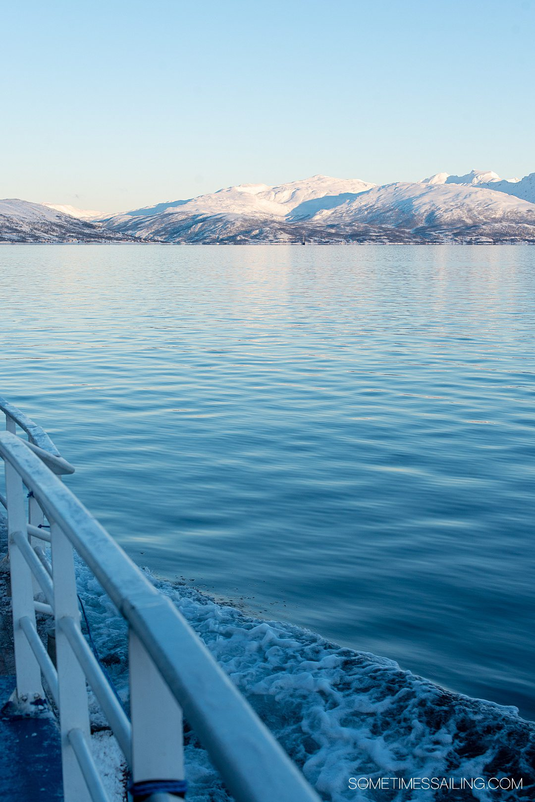 Snowy mountains in the distance and blue water in the polar region of Tromso, Norway.