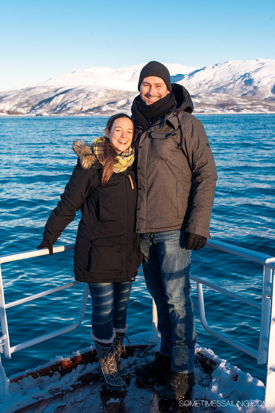 A couple at the stern of a ship on a Tromso, Norway boat tour with snowy mountains in the background.