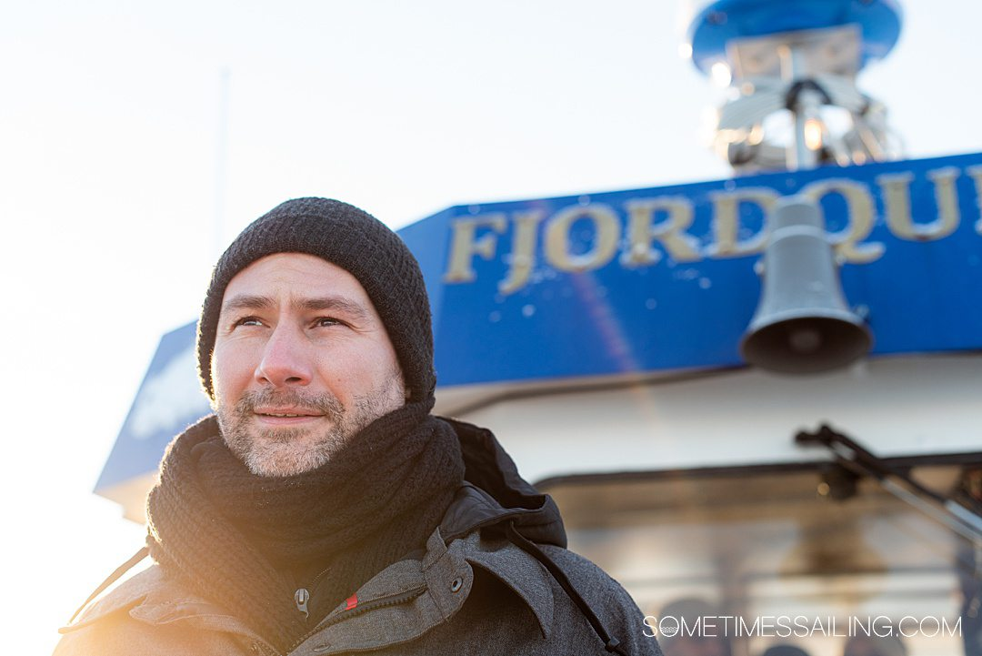"A man in front of the windshield of a boat with ""Fjord"" letters above."