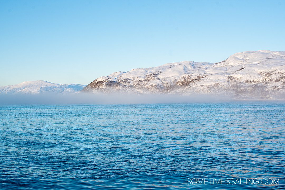 Blue water and snowy mountains with mist above the ocean on a Tromso, Norway boat tour.