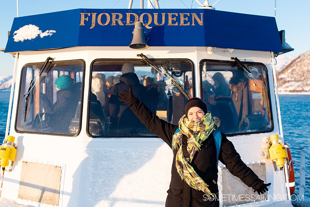 "A women in front of the windshield of a boat with ""FjordQueen"" letters above."