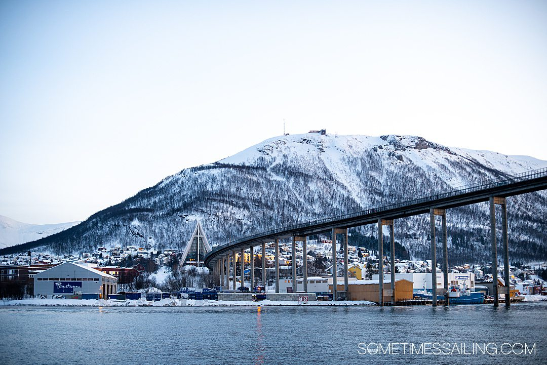 View of a bridge and Arctic cathedral as seen from a Tromso, Norway boat tour in the Arctic Circle.