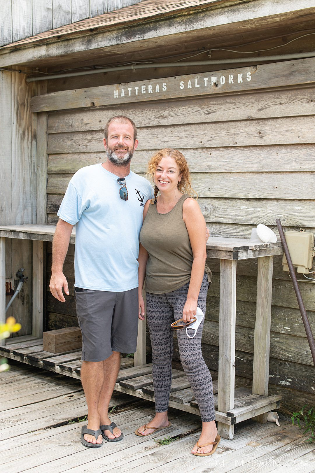 """A man and woman in front of a wood wall that says """"Hatteras Saltworks"""""""