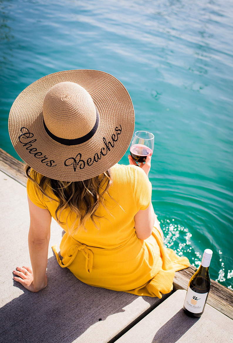 Woman's back in a yellow dress with a custom hat that says Cheers Beaches, holding a glass of red wine.