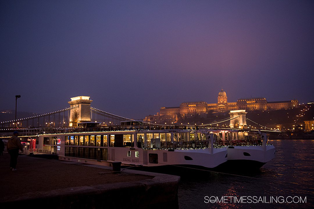 Bridge and castle in Budapest during night time, illuminated by lights for a Christmas Markets River Cruise post.
