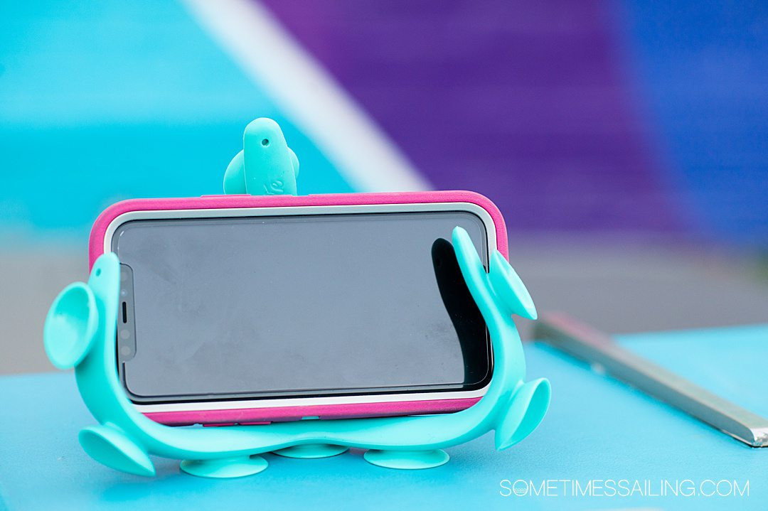 """Horizontal iPhone in a """"tenikle"""" tripod, great for a cruise gift, against a colorful background."""