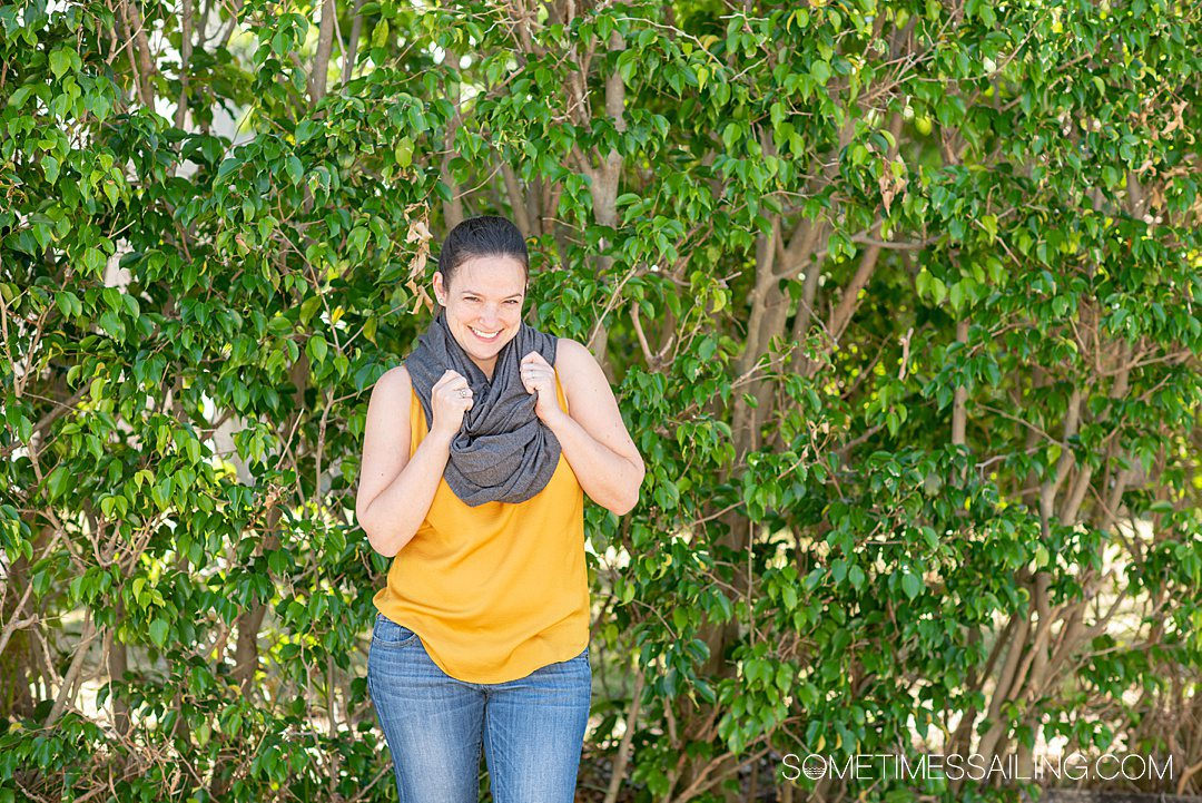 Woman in a grey wrap scarf that converts from to a blanket for best cruise gifts.