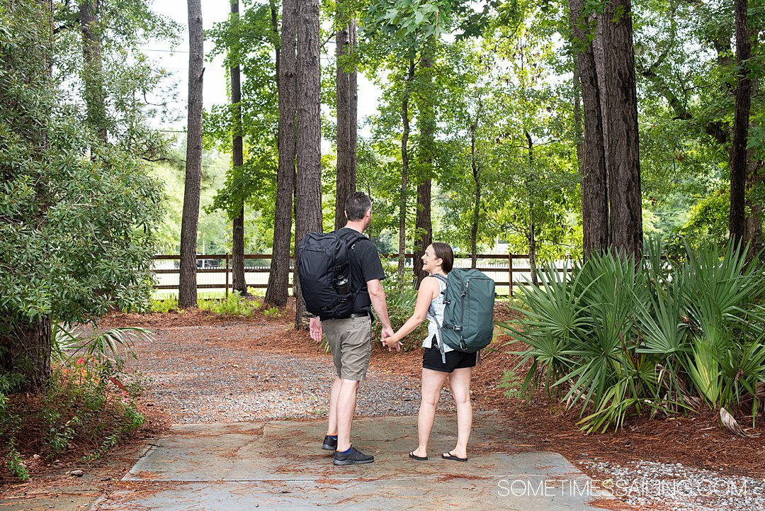 Man and a woman walking away with a black and green backpack on, respectively.