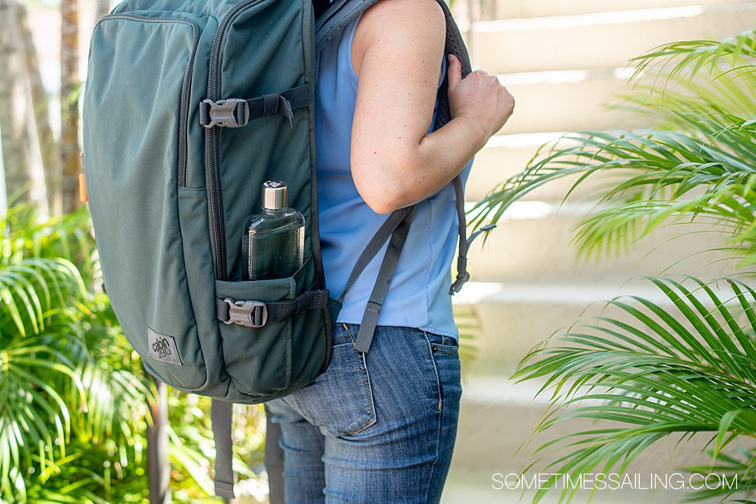 Moss green backpack with a reusable water bottle on the right side.