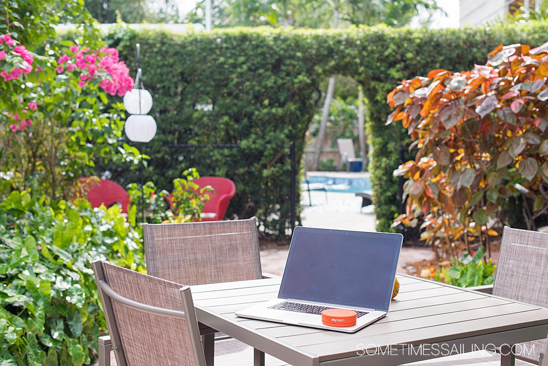 Laptop on a table with a round orange circle hotspot on it, and tropical greenery in the background.