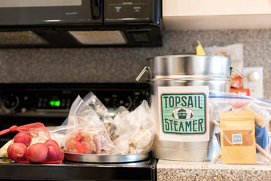 Contents of a seafood steamer pot for a Topsail Steamer review laid out on a counter with seafood, corn and potatoes inside in plastic bags.