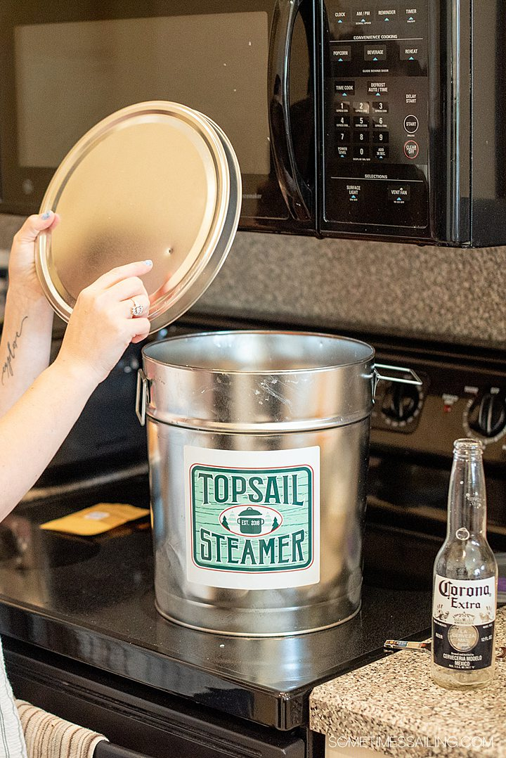 Adding the lid on a Topsail Steamer seafood pot on the stove.