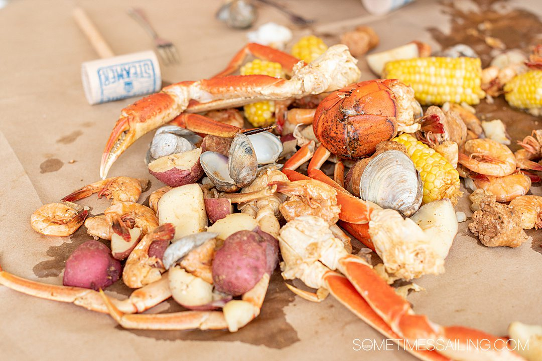 A bed of seafood and vegetables, including corn and potatoes, clams shrimp and crab legs.