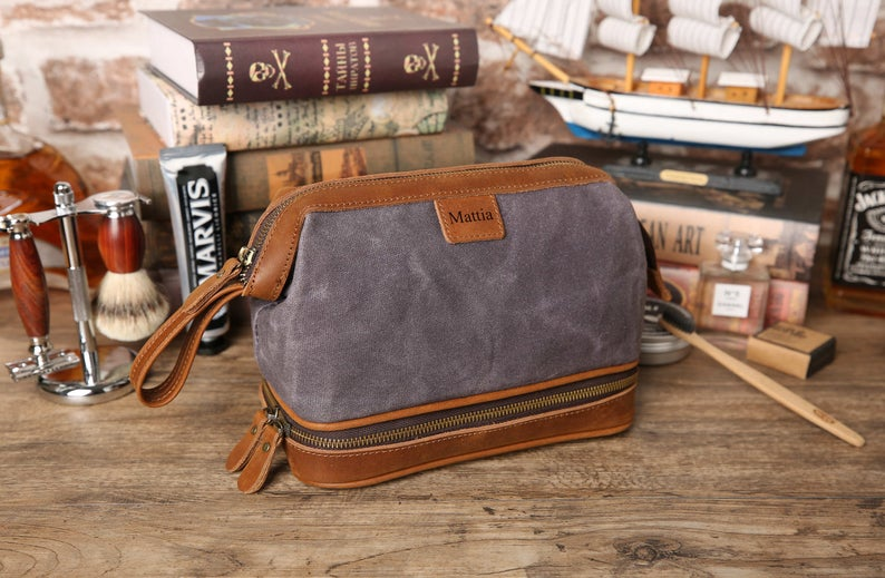 Brown leather and blue canvas toiletry bag with personalization for cruise gift ideas.