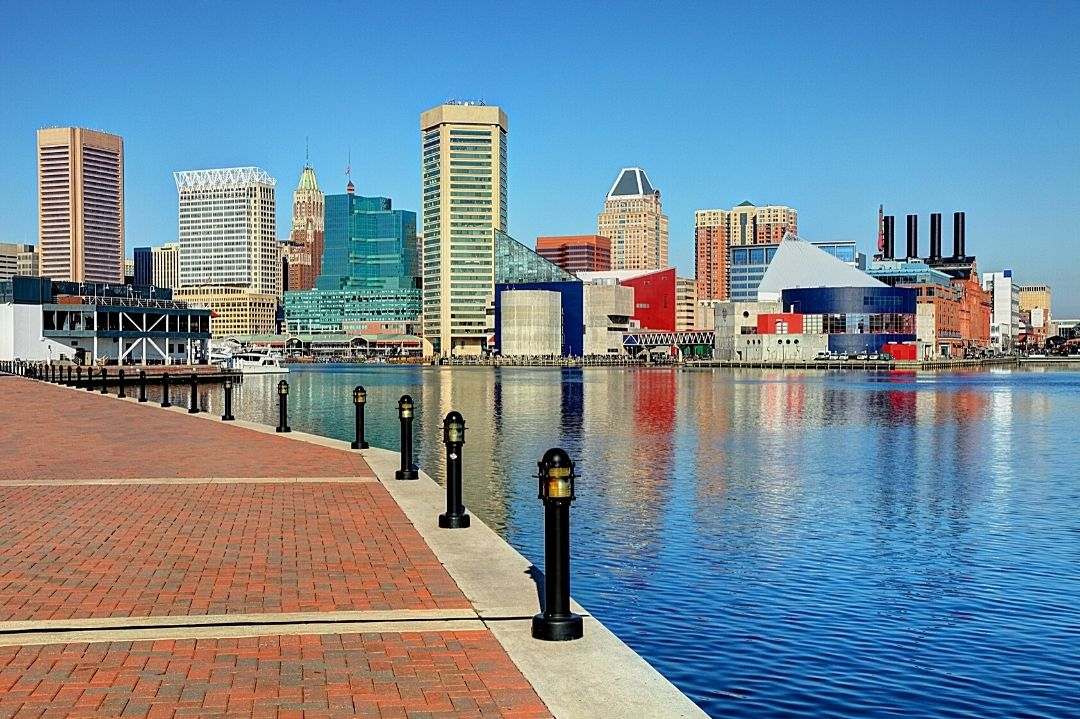 Inner Harbor in Baltimore with a view of the downtown Baltimore skyline in the distance.