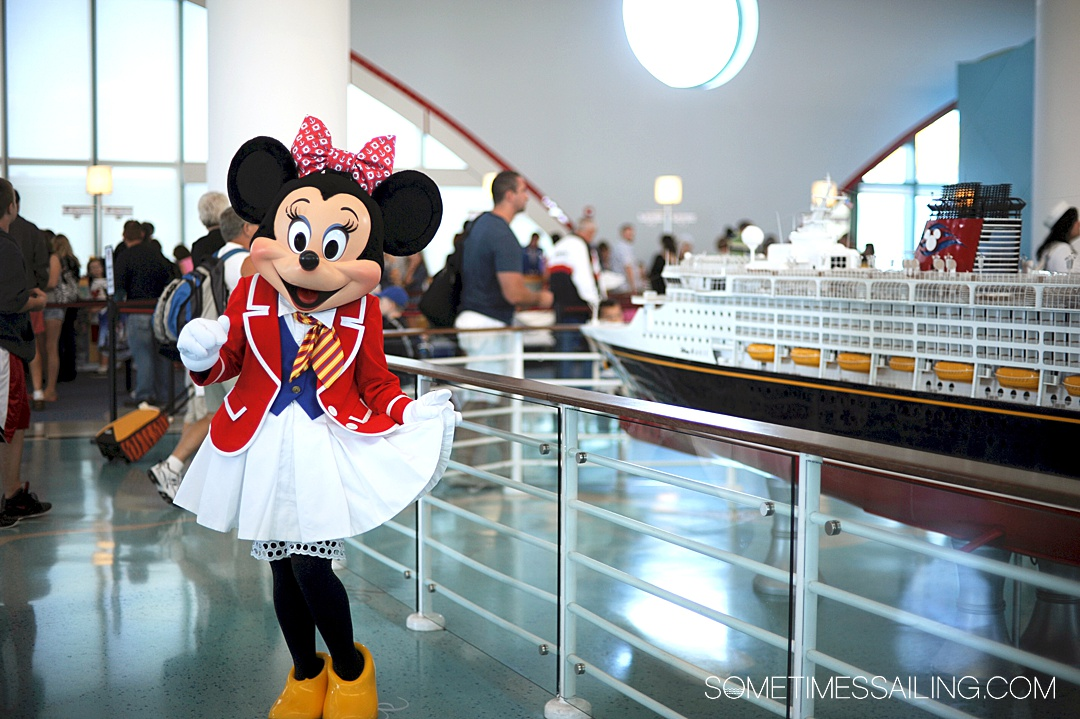 Minnie Mouse in a sailor outfit in front of a scale model of the Disney Cruise Line ship.