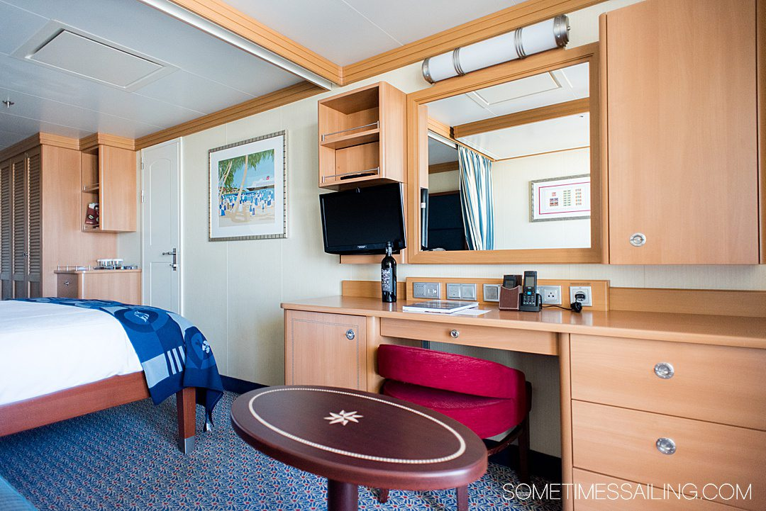 Interior of a cabin on the Disney Dream cruise line ship with a red chair and natural wood colored cabinets.