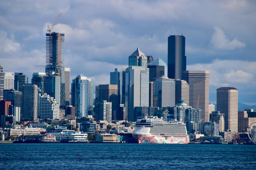 Cruise ship in the water with the Seattle, Washington skyline behind it.