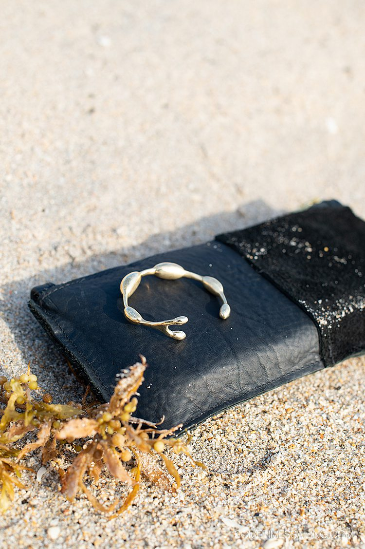 Brass seaweed bracelet on a black leather clutch in the sand, by Wildwood Oyster Co.
